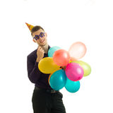 Wonderful young guy with a cone on his head keeps near the face paper glasses balloons and smiling Stock Image