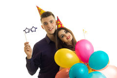 Wonderful young guy with a girl looking at camera smiling and carrying balloons and paper transfer Stock Images