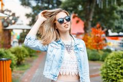 Wonderful young hipster woman in a stylish blue denim jacket in black sunglasses in a vintage lace blouse with a necklace royalty free stock image