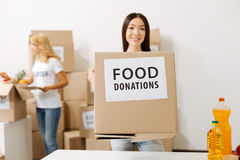 Wonderful young woman carrying a box with donations Stock Photography