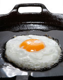 Wonderfull frying egg with oil in cast-iron pan
