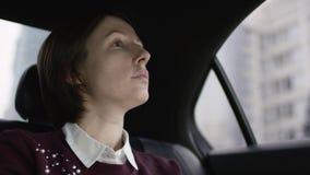 Wonderfullvrouw met bruin haar in witte blouse en het kastanjebruine sweater berijden in auto en het bekijken venster stock footage