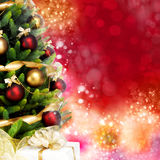 Wonderfully decorated Christmas Tree with balls, ribbons and garlands on a blurred red shiny and magical background Royalty Free Stock Photo