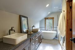 Wonderfully designed bathroom in a country house. Boasts dual washstand with dark granite countertop and rectangular vessel sinks royalty free stock image