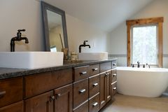 Wonderfully designed bathroom in a country house. Boasts dual washstand with dark granite countertop and rectangular vessel sinks royalty free stock photo