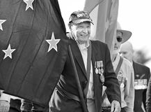 Old Australian Navy veteran leads Anzac Day parade flag bearer. A wonderfully happy and proud old elderly returned serviceman of the Royal Australian Navy armed royalty free stock image