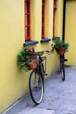 Wonderfully nostalgic scene of two rustic bikes propped against yellow stone building Royalty Free Stock Images