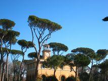 Wonderfully view in sunny spring weather in Rome in a park with a lot of pines and a nice building. Beautiful view in sunny spring atmosphere in rome in a park royalty free stock photo