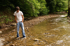 Wondering. A young teenager walking in a creek thinking royalty free stock photos