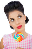 Wondering black hair model holding a colored lollipop Stock Photos