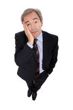 Wondering businessman. With hand on his face, isolated on white Royalty Free Stock Photography