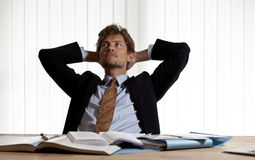 Wondering businessman leaning back in his chair Stock Image
