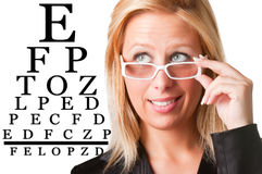 Wondering Businesswoman Looking at an eyechart. Worried bussinesswoman with glasses looking at an eyechart, isolated in a white background Stock Photo