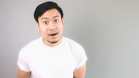 Wondering face on camera. An asian man with white t-shirt and grey background stock photography