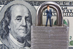 Wondering about Financial Security. Miniature business man standing on lock with 100 dollar bill in background Stock Photos