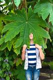 Wondering funny girl under huge green leaf. Tetrapanax papyrifer. Wondering funny girl with cheerful grimace face under huge green leaf of Tetrapanax papyrifera stock photos