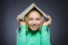 Wondering girl with book over head. Closeup Portrait of handsome teen shirt on grey background. studies concept Royalty Free Stock Images