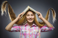 Wondering girl with book over head. Closeup Portrait of handsome teen shirt on grey background. studies concept Stock Photos