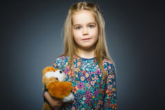 Wondering girl going surprise and playing with Toy dog isolated on gray Stock Photos