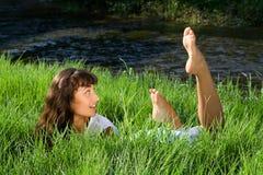 Wondering girl liying in fresh green grass Stock Photo