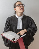 Wondering about the law. Thirty something brunette woman wearing a canadian lawyer toga with a red criminal law book in hand Royalty Free Stock Photos