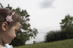 Wondering. Little girl wondering with a cloudy background Stock Photography