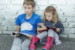 Wondering sibling children sitting on asphalt ground with books in hands. Wondering sibling children are sitting on asphalt ground with books in hands Royalty Free Stock Images