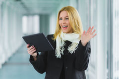 Wondering and successful business woman dressed in coat looking at tablet in hall Stock Images