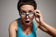 Wondering woman watching oover her glasses Royalty Free Stock Photography