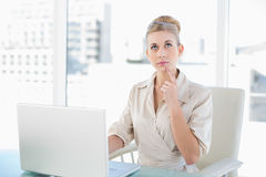 Wondering young blonde businesswoman using a laptop Stock Images
