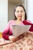 Wonderingly-Frau, die Leid nach readed Zeitung hat Lizenzfreie Stockfotografie