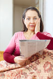 Wonderingly  woman having grief after readed   newspaper Royalty Free Stock Photography