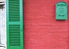 Wondow con l'otturatore verde nel rosso variopinto ha dipinto la vecchia parete rossa immagine stock