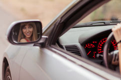 Wonen in car. Fashionable girl sitting in a gray car. Her smiling face reflected in the side mirror Stock Photography