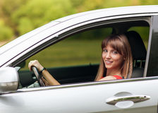 Wonen in car. Girl driving a gray car Royalty Free Stock Photography