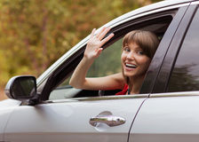 Wonen in car. Girl driving a gray car. Welcomes the raised hand Stock Images
