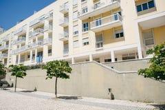 Woningbouw met balkons in Lissabon in Portugal Dichtbij het gebouw is er een straat met bomen stock afbeelding