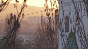 Woningbouw met meerdere verdiepingen in de afstand bij zonsondergang in een lichte nevel stock videobeelden