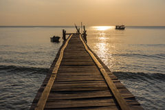 A wonky wooden jetty pier goes out in to a calm sea with small b Stock Images