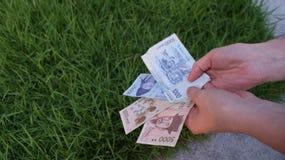 Wons coreani dei soldi nelle mani fotografia stock