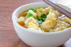 Wonton dumpling in clear soup. Wonton Soup Dumplings in a bowl on a wooden table stock photo