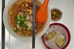 Wonton noodles. Is a Cantonese noodle dish which is popular in Guangzhou, Hong Kong, Malaysia, Singapore and Thailand. The dish is usually served in a hot broth stock photo