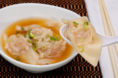 Wonton Soup. Bowl of wonton soup with selective focus on spoon royalty free stock image