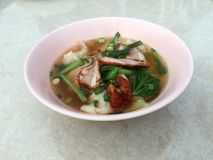 Wonton soup and Barbecued red pork with green Vegetable in the p stock image