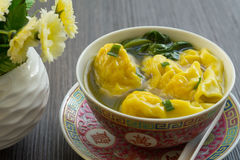 Wonton Soup. Boiled wontons served with broth and Chinese greens garnished with chives royalty free stock image