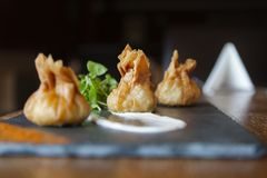 Wontons on a slate plate in a restaurant. Royalty Free Stock Photos