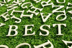 Wood alphabet as wording best on artificial green grass. Background Stock Images
