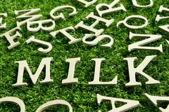 Wood alphabet as wording milk on artificial green grass. Background Royalty Free Stock Photos