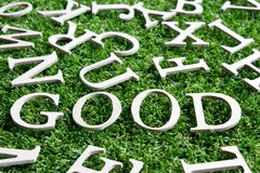 Wood alphabet in wording good on artificial green grass stock image