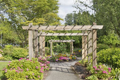 Wood Arbor Over Garden Path. With Plants Trees and Flowers Blooming in Summer Royalty Free Stock Photography